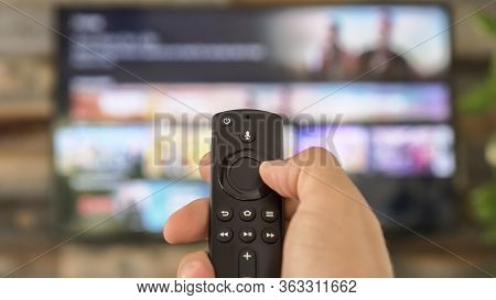 Male Hand Holding The Tv Remote Control And Changing Tv Channels