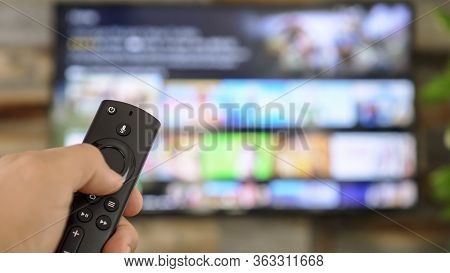 Male Hand Holding The Tv Remote Control And Changing Tv Channels. Channel Surfing, Focused On The Ha
