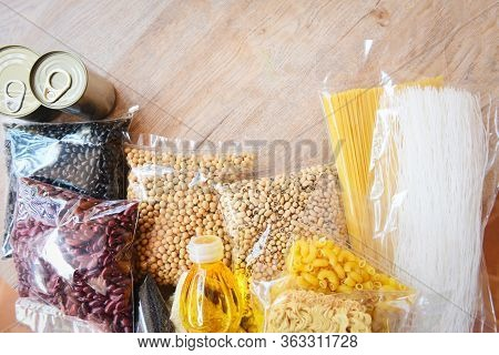 Donations Food With Canned Food On Wooden Table Background / Pasta Canned Goods And Dry Food Non Per