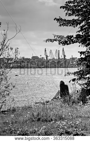 A Lonely Girl Sits On The Grass And Looks At The Harbour Of Tallinn, The Capital Of Estonia. The Spr