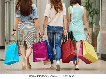 Back View Of Three Stylish Women With Paperbags After Shopping