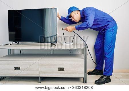 Serious Young Vietnamese Repairman Installing Tv Set In Apartment Of Customer