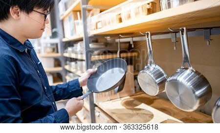 Asian Man Customer Choosing Nonstick Frying Pan Or Frypan In Kitchenware Store. Buying Cookware For