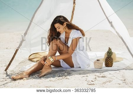 Attractive Woman Sitting On A Deserted Beach Under The Handmade Tent. Gorgeous Slim Mixed Race Asian