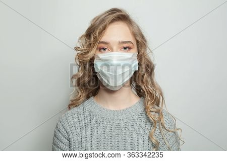 Beautiful Woman In A Face Mask On White Background. Woman In Medical Mask. Flu Epidemic And Virus Pr