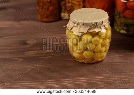 Marinated Canned Mushrooms Champignon In Front Of Variety Of Mixed Conserved Vegetables. Organic Con