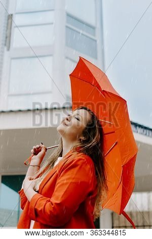 Mental Health Concept. Portrait Of Young Happy Woman In Red Under Red Umbrella Breathing In The Stre