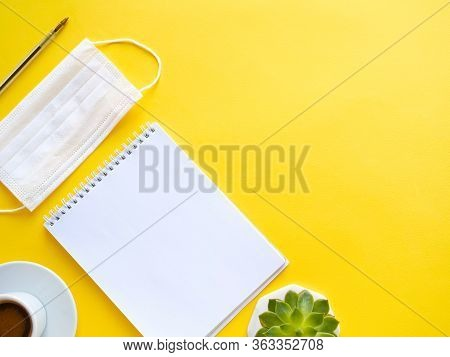 Flat Lay Composition With Notebook, Mask, Pen, Coffee, Plant On Yellow Background. Concept Remote St