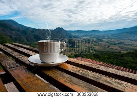 A White Cup Of Coffee With Smoke On Wood Table, Blurred Estate Scenic Background, High Angle View. M