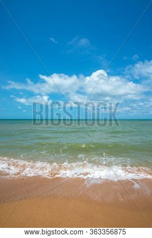 Landscape Scenery Of Sea Wave With White Bubble Splashing On Beach With Blue Sky.it Is A Quiet Beach