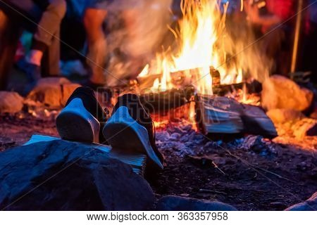 Closeup Camp Fire At The Night . A Pair Of Camp Shoes Is Dried Near A Fire In The Forest