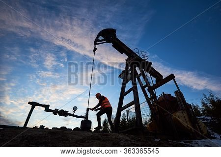 Side View Silhouette Of Oil Man In Work Vest And Helmet Repairing Petroleum Pump Jack. Oil Worker Us