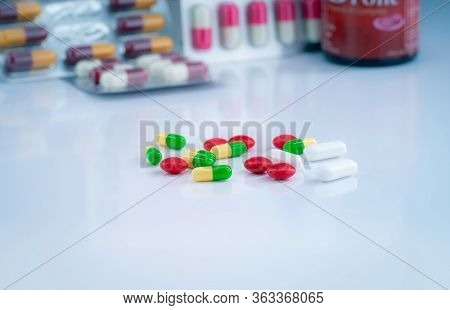 Colorful Tablets And Capsule Pills On Blurred Background Of Drug Glass Bottle And Blister Pack. Phar