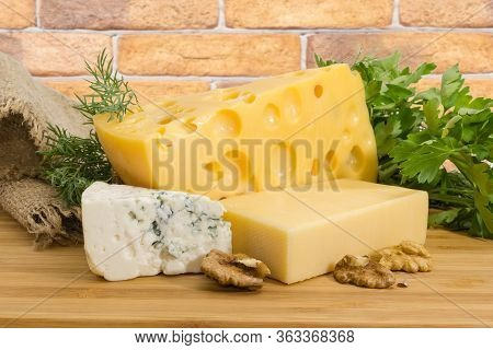 Pieces Of Medium-hard Swiss Cheese, Hard Cheese, Blue Cheese Among The Greens And Walnut Kernels On
