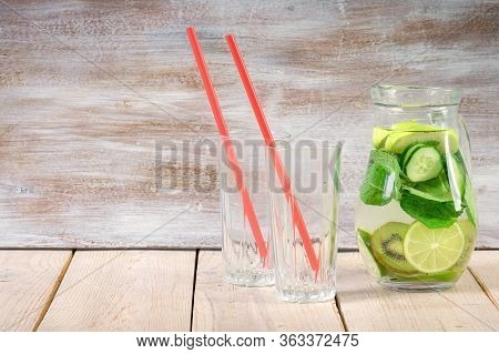 Two Glasses Of A Cold Fresh Lemonade Drinks With Slices Of Lime On The Glass, And Carafe. Slices Of