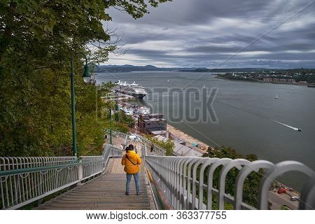 Quebec City, Canada September 23, 2018: Photographer In An Orange Jacket At The Stairs Photo Taken O