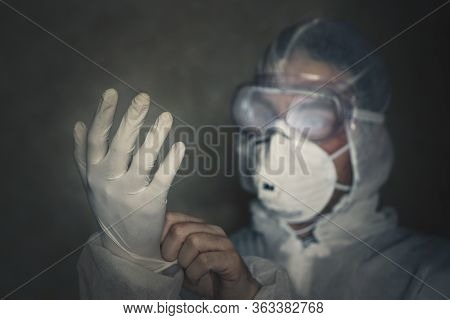 Man Puts On A Protective Antiviral Suit. Puts Gloves On Hand Close-up. In Dark Room. Work At Night.