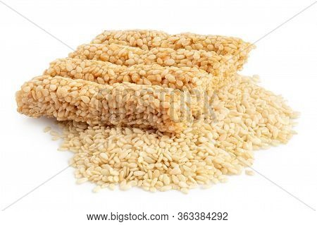 Square Sesame Seed Honey Bar On A Pile Of Peeled Sesame Seeds Isolated On White.