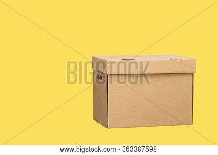 Cardboard Box Isolated On A Yellow Background. Carton Packaging Box. Donation Box