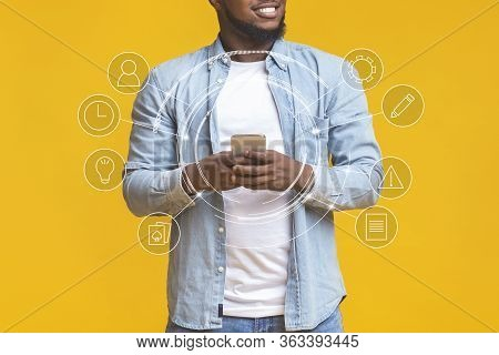 Mobile Functions Concept. Black Man Using Smart Phone, Collage With Functional Buttons, Yellow Studi