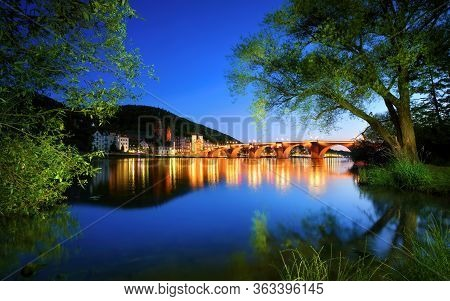 Neckar River In Heidelberg, Germany, At Dusk, With Deep Blue Sky Reflected In The Clear Water And Gr