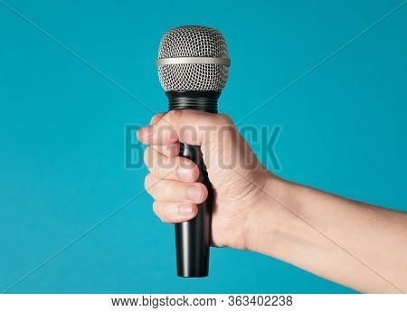 Hand Holding Up A Microphone Isolated Against A Bright Blue Background
