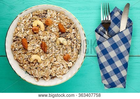 Oatmeal With Nuts On A White Plate With Fork And Knife. Oatmeal On Aturquoise Wooden Table. Oatmeal