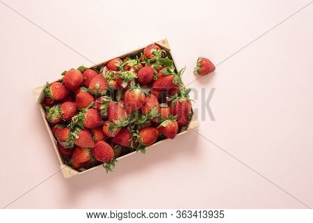 Fresh Strawberries In A Wooden Box On A Pink Table Above View. Homegrown Strawberries Harvested In A