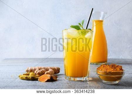 Golden Milk Turmeric Iced Freshness Latte Garnish Mint Sprig. Ayurvedic Drink On Light Background. S