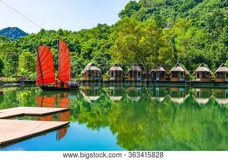 Junk. Beautiful Traditional Vietnamese Boat With Red Sails On A Picturesque Lake In The Jungle. Many