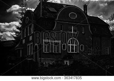 An Old,dark House Below A Cloudy Sky