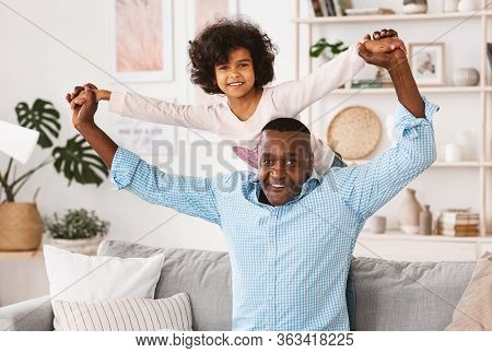 Playtime With Granddad. Mature African American Man Playing Funny Game With His Granddaughter At Hom