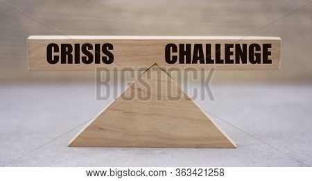 The Concept Of The Balance Of Words Between Crisis And Challenge On Wooden Scales On A Light Backgro