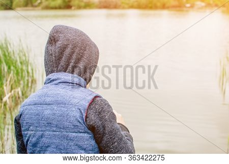 The Child In The Blue Yolk And Hood Looks Into The Distance. The Boy Faces The River And Looks At Th