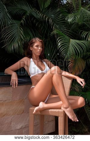 Beautiful Brunette Girl In White Swimsuit Posing In Tropical Location With Green Trees. Young Sports