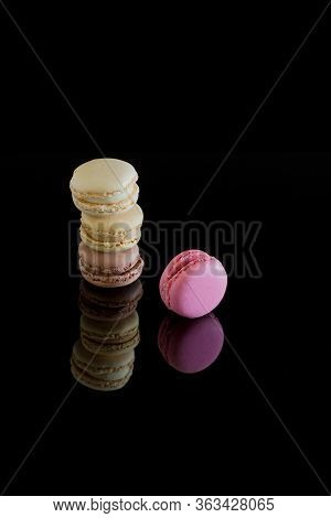 Colorful Macarons With Reflection Isolated On A Black Background. Sweet French Cakes.
