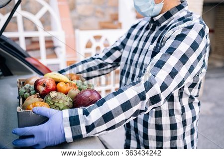 Male Volunteer Bringing Fruits And Vegetables To A Senior Woman At Home.helpful Concept.