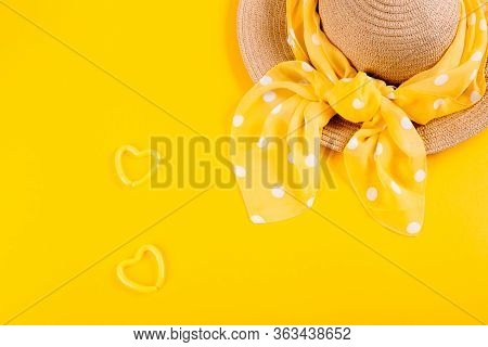 A Straw Hat With A Polka Dot Scarf On A Yellow Background With An Empty Place For Advertising And Te