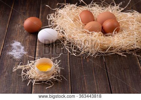 An Open Egg With The White And Yolk On The Hay, In The Background In A Nest Of Hay Are Whole Fresh E