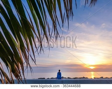Silhouette Of A Woman In The Blue Shirt On The Pink Sunset Background And With Palm Leaves