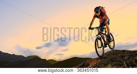 Cyclist in Red Riding the Bike Down the Rock in the Beautiful Mountains on the Sunset. Extreme Sport and Enduro Biking Concept.