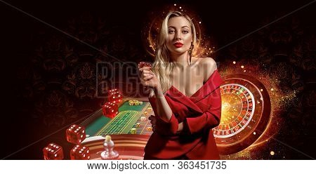 Girl In Red Dress. Showing Chips, Posing On Dark Background. Roulette, Playing Table With Stacks Of