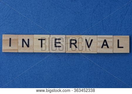 Text On Gray Word Interval Of Small Wooden Square Letters Lies On A Blue Paper Table