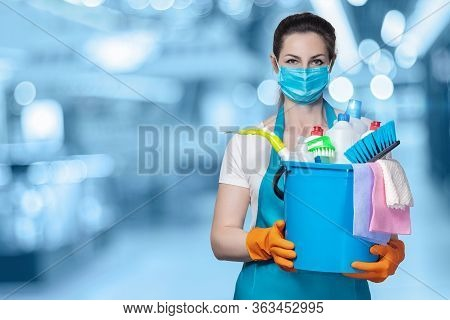 The Concept Of Disinfection And Cleaning. The Lady In The Mask With A Bucket Of Cleaning Products On