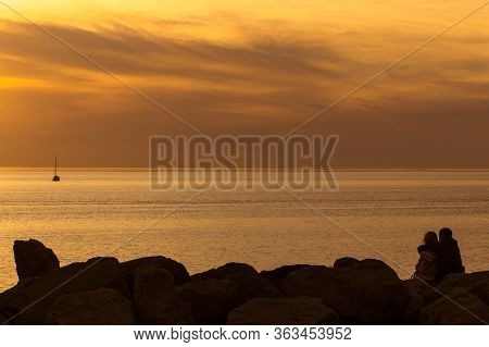 Silhouettes Of Loving Couple Are Sitting On The Stones Closeup At Sunset Time Near The Sea