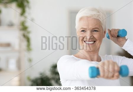 Portrait Of Happy Elderly Woman Exercising With Dumbbells At Home, Having Active Lifestyle On Retire