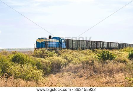 Diesel Locomotive With Freight Cars On A Field Background With Green Grass
