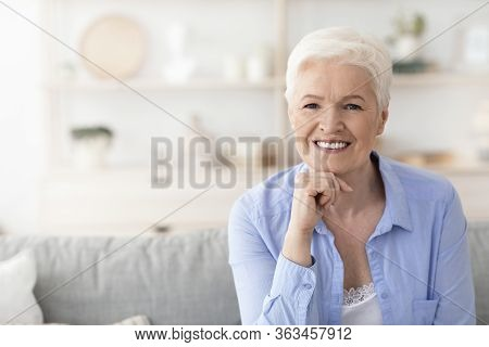 Carefree Retirement. Portrait Of Happy Beautiful Senior Woman Posing At Home, Sitting On Couch And S
