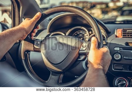 A Man Drives A Car While Holding His Hands On The Steering Wheel.