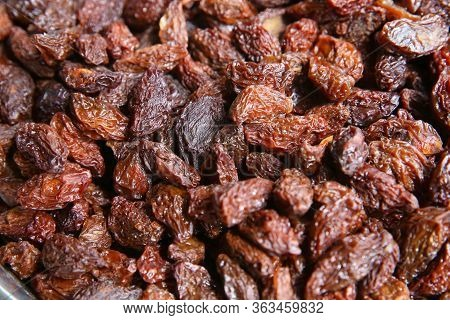 Black Raisins In The Wooden Bowl. Sweet Dry Raisins Close-up Shot For Background . Many Raisins For